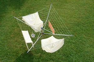 Wäschespinne mit Textilien auf Rasen